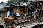 A police officer and a rescue dog look for bodies in an area destroyed after mudslides in Manizales.