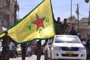 Kurdish People's Protection Units (YPG) fighters wave their flag in northeastern Syrian town of Qamishli.