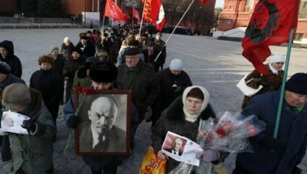 Communist supporters hold flags and portraits of Soviet State founder Vladimir Lenin during a wreath laying ceremony at the Lenin