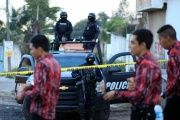 Police keep watch on the perimeter of a murder scene in Mexico.