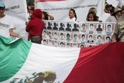 People hold a Mexican flag during a demonstration to demand information on the 43 missing students of the Ayotzinapa teachers' training college.