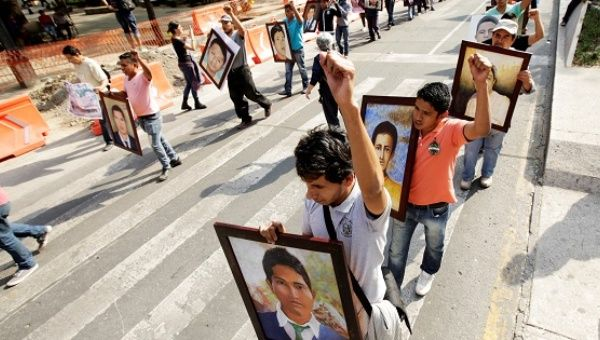 Relatives and activists hold paintings during a protest to demand justice for the 43 missing students of Ayotzinapa, in Mexico City.