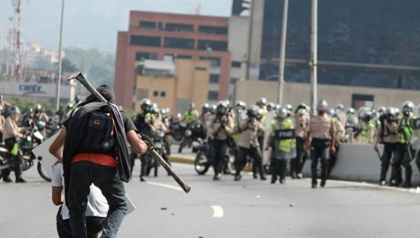 Two protesters tease and menace approaching Venezuelan National Police.