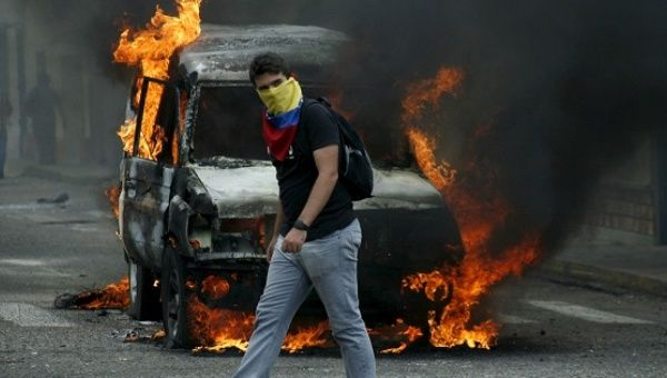 An opposition protester wearing a Venezuelan national flag to cover his face walks in front of a burning van during a protest against President Nicolas Maduro