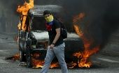 An opposition protester wearing a Venezuelan national flag to cover his face walks in front of a burning van during a protest against President Nicolas Maduro's government.