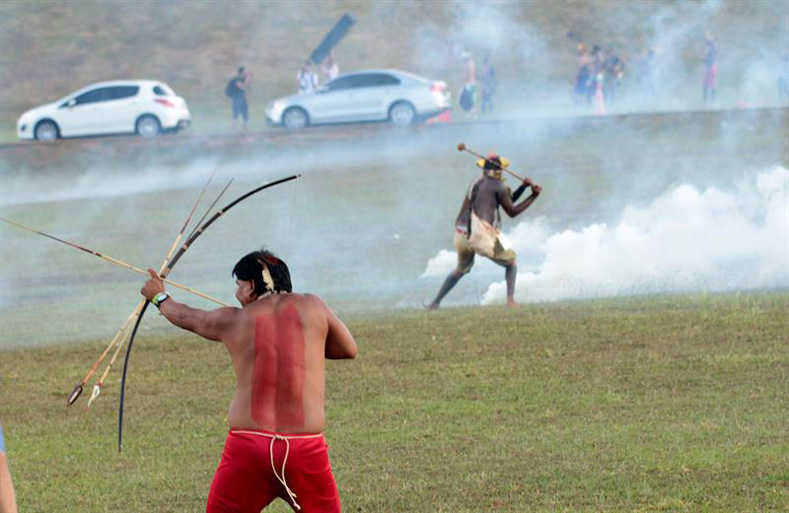 Brazilian Indigenous people fire arrows toward police who were attacking a demonstration against the violation of Indigenous people