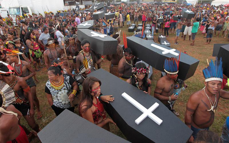 Brazilian Indigenous people carry a symbolic coffin, to show the death of Indigenous people