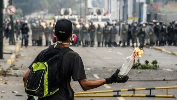 A Venezuelan opposition supporter holds a lit Molotov cocktail during clashes with riot police in Caracas on April 10, 2017.