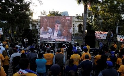 People watch on TV as congress members discuss a proposed amendment to allow presidential second terms in Asuncion.