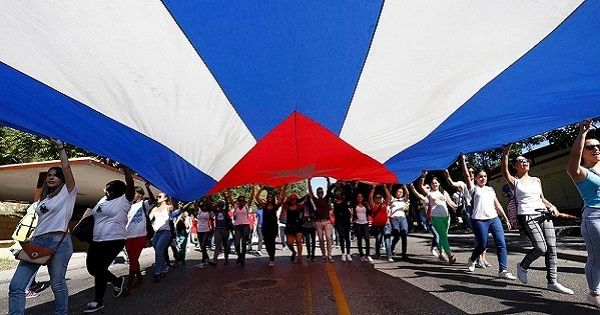 Students of Havana University carry a large Cuban flag as they march in tribute to Cuba