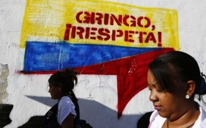 Venezuelan women walk past a mural in Caracas.