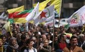 Kurds carry flags as they protest, in the northeastern city of Qamishli, against Turkish airstrikes on the headquarters of the Kurdish fighters from the People
