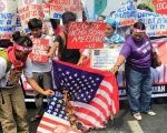 Protesters burn a U.S. flag and pictures of President Donald Trump outside the U.S. embassy in Manila.