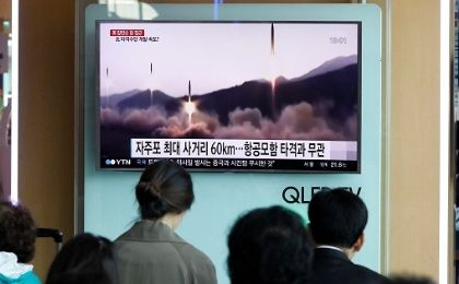 People watch a TV broadcast of a news report on North Korea