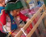 A Peruvian women weaves a traditional fabric to sell in markets.