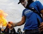 A demonstrator prepares to throw a molotov cocktail while rallying against Venezuela's President Nicolas Maduro in Caracas.
