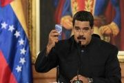Venezuela's President Nicolas Maduro holds a copy of the Venezuelan Constitution as he speaks during a ceremony at Miraflores Palace in Caracas.