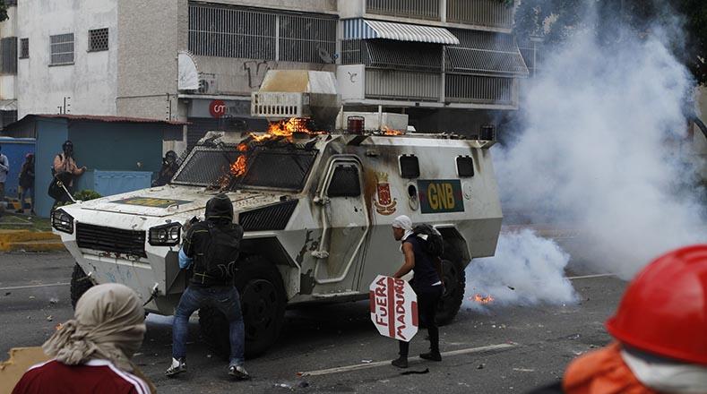 Un grupo de jóvenes arremete contra un vehículo de la GNB.