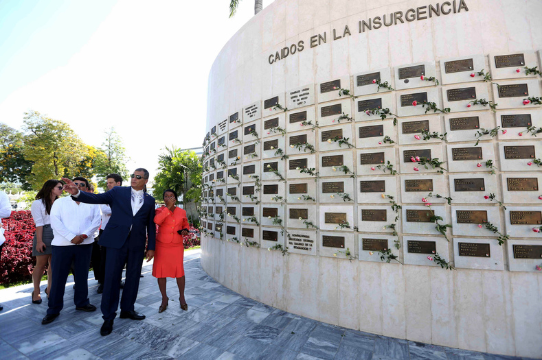 Correa walks past a monument to those who fell during the insurgency.