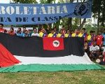 Athletes pose at the Dr. Socrates Brasileiro Field along with the flag of Palestine.