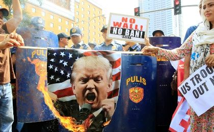 Filipino activists burn a portrait of U.S. President Donald Trump during a protest against U.S. immigration policies outside the U.S. embassy in metro Manila, Philippines, Feb. 4, 2017.
