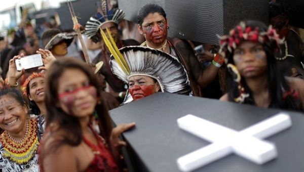 Indigenous people carry mock coffins during a demonstration against the violation of Indigenous people