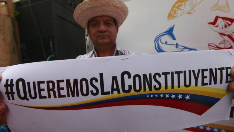 "A campesino holds a banner with the message ""We want the constituent."""