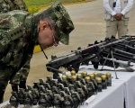 Colombian army officers examines seized grenades and weapons from the FARC in July, 2013. (FILE)