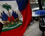 A flag from Haiti is pictured in a local store as a woman walks under rain at the neighborhood of Brooklyn in New York.
