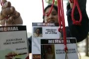 A woman hangs media accreditations with the names of journalists killed while covering the news in Mexico.