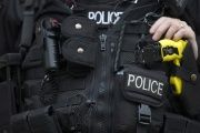 An armed police officer rests his hand on a taser outside the Ministry of Defence in London, Nov. 18, 2015.