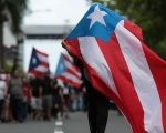 A person carries a Puerto Rican national flag in San Juan during a protest against the government's austerity measures.