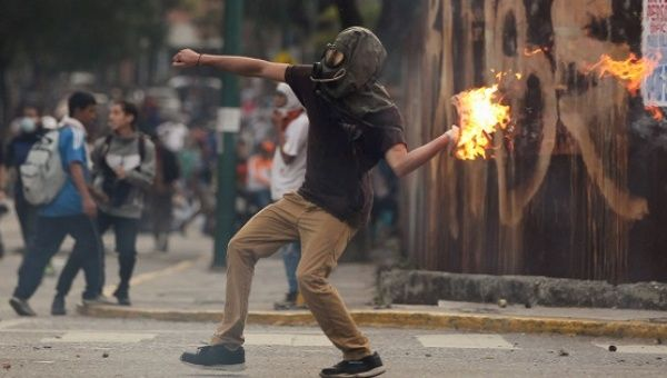 A demonstrator throws a molotov cocktail at police in Caracas.