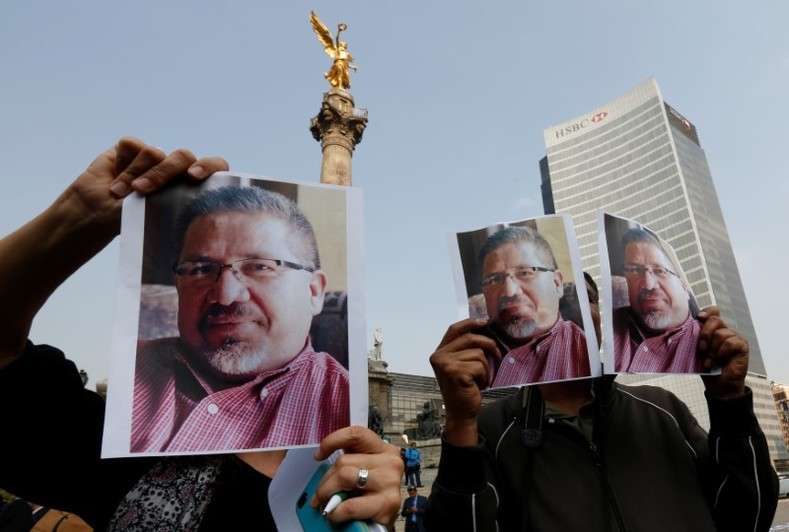 Journalists and photographers hold up pictures of journalist Javier Valdez during a demonstration against his killing and for other journalists who were killed in Mexico, at the Angel of Independence monument in Mexico City, Mexico May 16, 2017.