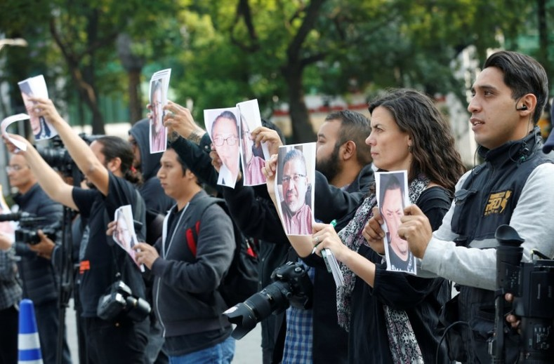 Journalists and photographers hold up pictures of journalist Javier Valdez during a demonstration against his killing and for other journalists who were killed in Mexico, at the Angel of Independence monument in Mexico City, Mexico, May 16, 2017.