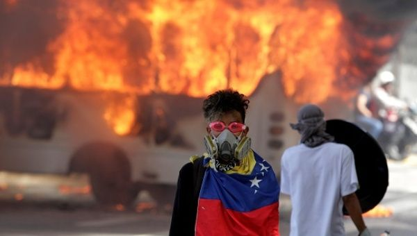 A protesters stands in front of a burning bus during protests in Caracas.