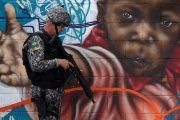 A Brazilian policeman patrols the streets near the Chapadao favela complex during a security operation on an effort to crack down on crime in Rio de Janeiro.
