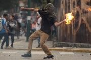 A right-wing protester hurls a Molotov cocktail as violent opposition protests continue into their seventh week.