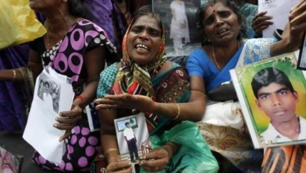 Tamils with images of family members who vanished during the Sri Lanka civil war, at a protest in the north in Jaffna, Aug. 2013.
