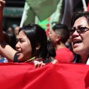 Aurora Victoria David (center, raised fist) marches with her mother (right) in San Francisco, California, on International Worker