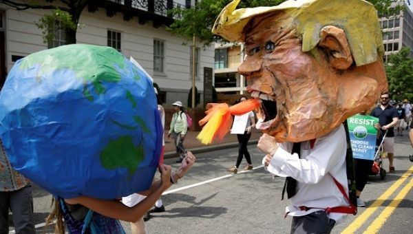 Protesters dressed as the earth and U.S. President Donald Trump pretend to fight during the Peoples Climate March near the White House in Washington, U.S., April 29, 2017.