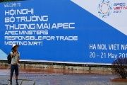A man stands in front of a banner welcoming APEC trade ministers for a meeting in Hanoi, Vietnam, on May 19, 2017.