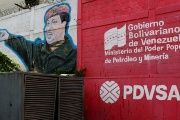 The logo of the Venezuelan state oil company PDVSA is seen next to a mural depicting Venezuela's late President Hugo Chavez at a gas station in Caracas, Venezuela.