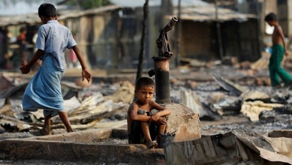 A boy sits in a burnt area after fire destroyed shelters at a camp for internally displaced Rohingya Muslims in Rakhine State, Myanmar, on May 3, 2016.