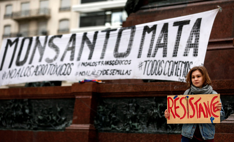 "A demonstrator holds a sign in front of a banner that reads ""Monsanto kills"" during a protest against giant seeds company Monsanto, in Buenos Aires, Argentina, May 20, 2017."