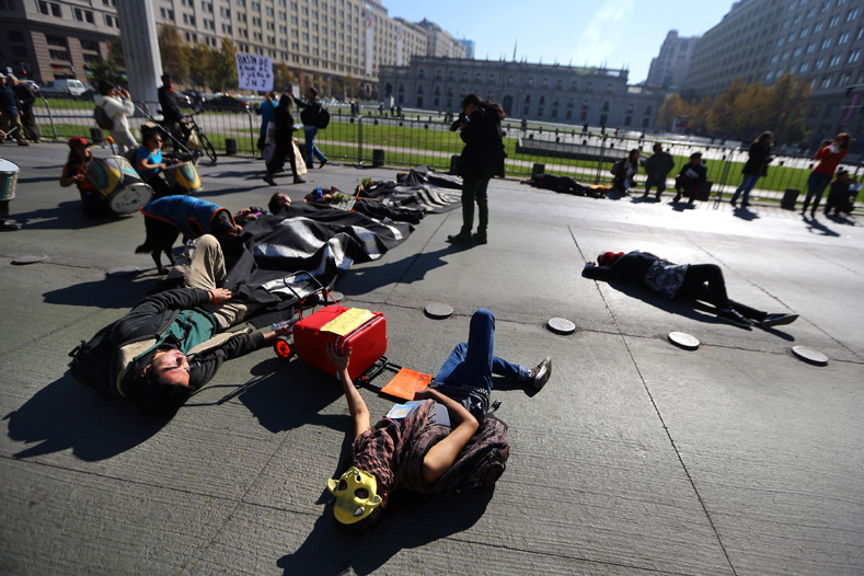 Demonstrators pretending to be dead lie on the ground during a protest against seeds company Monsanto in Santiago, Chile, May 20, 2017.