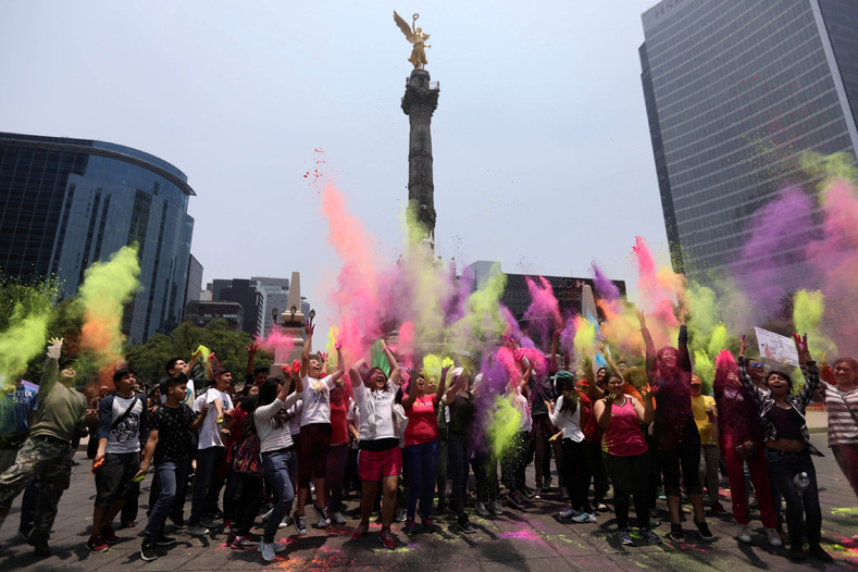 "People and activists throw in the air different coloured powders as they take part in a demonstration against U.S. seeds and agrochemicals company ""Monsanto"" at Angel de la Independencia monument in Mexico City, Mexico, May 20, 2017."