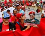 A pro-government supporter holds up a sign of Venezuela's late President Hugo Chavez during a rally of members of the education sector in Caracas, Venezuela June 14, 2016.