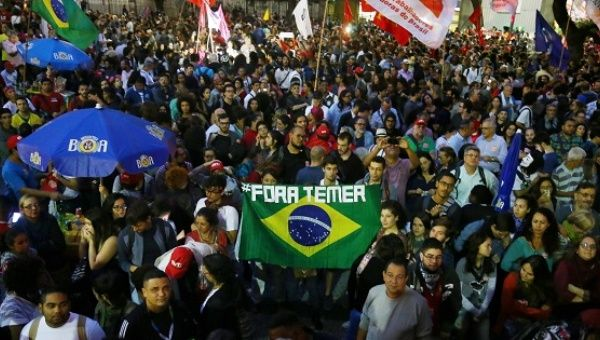 Demonstrators carry a Brazilian national flag as they attend a protest against Brazil