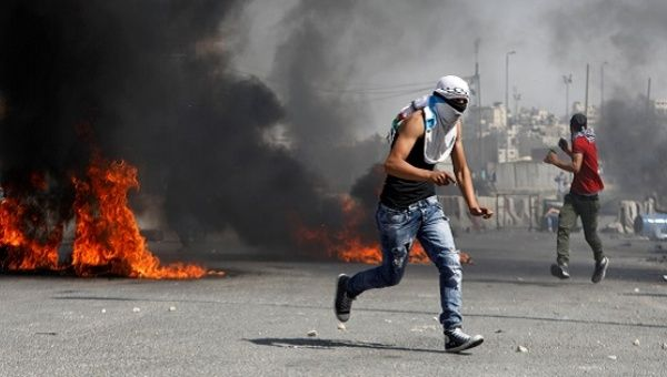 A Palestinian protester runs for cover during clashes with Israeli troops at a protest in support of Palestinian prisoners on hunger strike in Israeli jails.